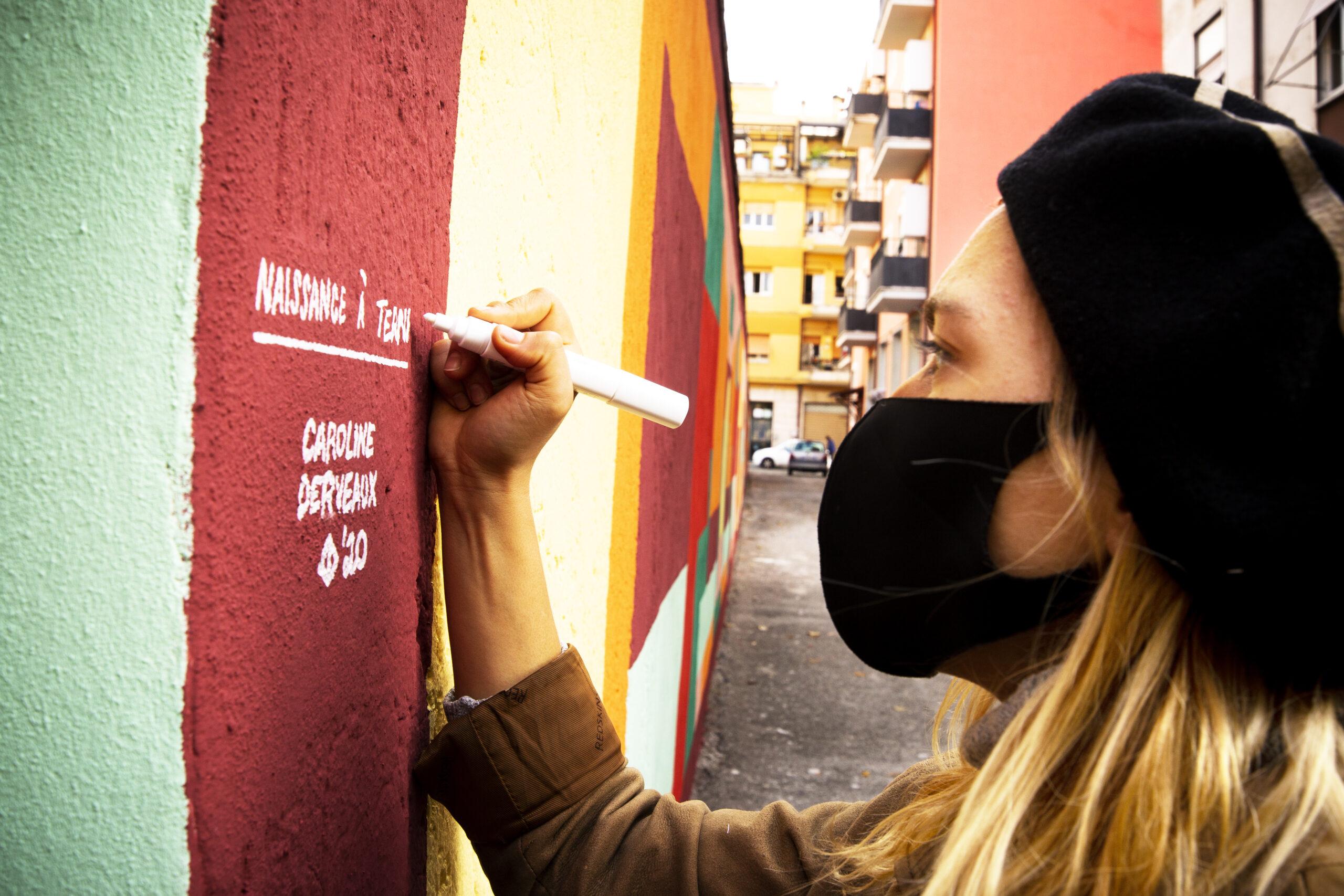 Caroline Derveaux firma il muro dove ha appena realizzato la sua opera Naissance